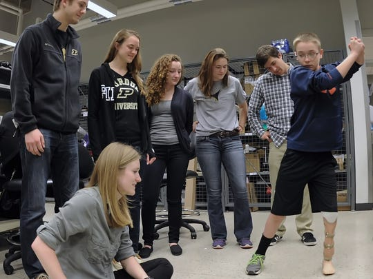 The Purdue build team, Haley Smith, seated, Quinton Lasko, Jennie Boehm, Rachel Berry, Ally Gleason and Sami Labban watch intently as Alex puts his new prosthetic leg through a batter's range of motion.
