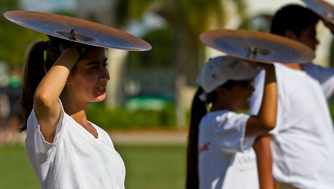 Komila Khamidova, 16, shades herself from the sun with her cymbal during a marching band practice Tuesday afternoon at Fort Myers High School.