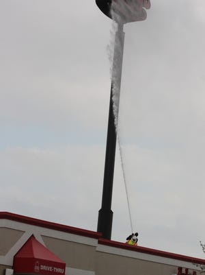 Williamsburg firefighters take to the roof to extinguish a fire from within the sign at Arby's, at Tanger Outlet Center Tuesday afternoon, April 19.