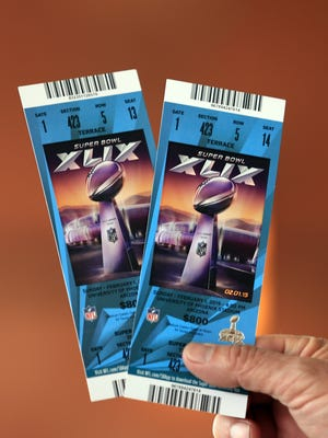 A fan holds Super Bowl XLIX tickets at the StubHub ticket center in the Glendale Renaissance.