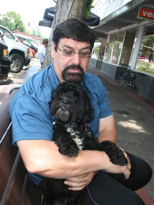 Russ Gaylor, a volunteer with the Willamette Humane Society, cuddles with Oliver, a poodle/terrier mix who will be up for adoption after the dog helps with the shelter's summer camps.