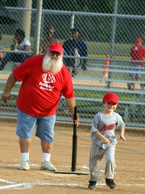 """Volunteer Coach Daryl """"Snapper"""" Parker works with one of the kids in the Buddy Ball at Heritage Park."""