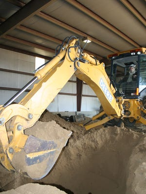 Alec Welborn, then 17, takes the controls of a John Deere rubber tire backhoe on Nov. 11, 2010 at the Local 234 Operating Engineers Training Center outside Indianola as part of a construction trades pre-apprenticeship program.
