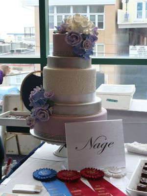 Nage shows off its five-tiered hydrangea showpiece cake along with four ribbons won at the event