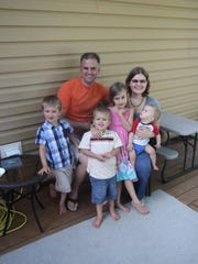 Patrick and Destiny Hoerter smile with their four children at their home in Wausau.