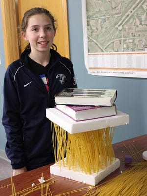 Emma Johansen shows how strong spaghetti can be when it works together during the Introduce a Girl to Engineering Day event at the Foth Companies in Johnston.