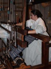 Interpreter Amanda Beatty demonstrates weaving in the Craftsman's House.