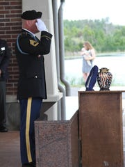 A member of the Honor Guard salutes the urn holding