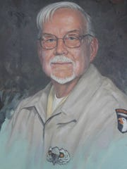 A painting of Donald Burgett adorned a table showcasing his World War II experience. His ashes were interred Tuesday during a memorial service at the Great Lakes National Cemetery in Holly.