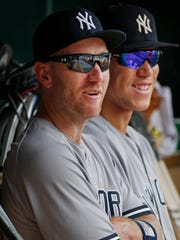 New York Yankees third baseman Todd Frazier sits in the dugout with Aaron Judge during a baseball game against the Minnesota Twins Wednesday, July 19, 2017, in Minneapolis. The Yankees acquired Frazier on Tuesday in a trade with the Chicago White Sox. (AP Photo/Bruce Kluckhohn)