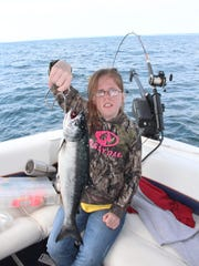 Megan Hartwig, 13, of Clintonville, Wis. holds a coho salmon she caught on a Lake Michigan fishing outing organized by United Special Sportsman Alliance, Inc., a non-profit organization based in Pittsville, Wis.