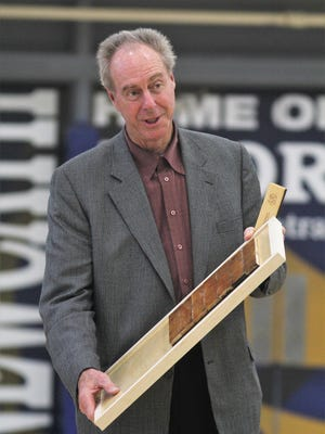 Dave Cowens with a plaque featuring a piece of the original gymnasium floor, at the dedication of Newport Central Catholic's new gymnasium floor August 20, 2018.