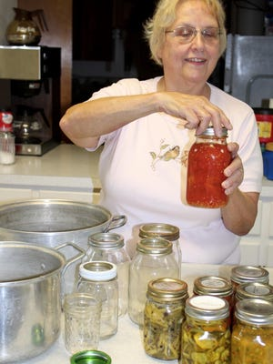 Brenda Sprow checks the lid of a canning jar of tomatoes she grew in her garden this summer.