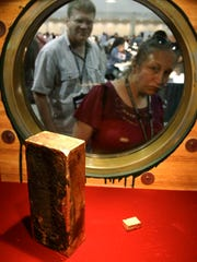 In this Aug. 10, 2010 file photo, coin collector Darlene Corio, of Rochester, N.Y., right, peers through a circular window at a gold ingot weighing more than 662 ounces as her husband, Tim Corio, left, looks on at a display at the World's Fair of Money in Boston. The ingot was among two tons of California Gold Rush gold recovered from the shipwreck of the S.S. Central America which sank in 1857. (AP)