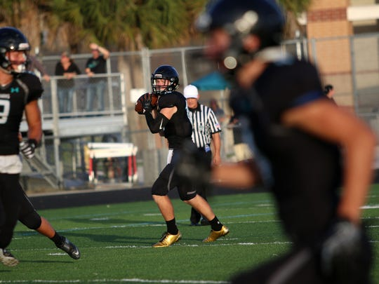 Kaden Frost looks for the open pass during Friday night's spring game between Gulf Coast and Sarasota in Naples. Gulf Coast blew past the Sailors with a 35-0 win.
