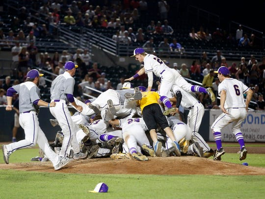 Johnston players pile on the mound as they celebrate