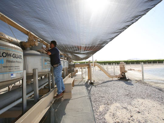 Adrian Zendejas, general manager of Desert Mist Farms checks the irrigation filtration equipment in one of the company's Coachella fields, Tuesday, April 15, 2015.
