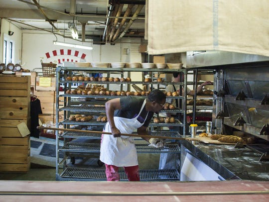 Calito Ambois checks on loaves in the oven at O Bread