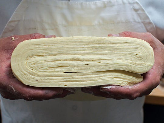Baker Josh Lemieux shows layers of folded yeasted dough and butter as he makes laminated croissant dough at the Williston Coffee Shop in Williston on Tuesday, September 27, 2016.