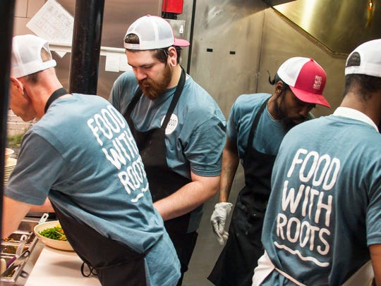 Cooks work on the line during the lunch rush at the