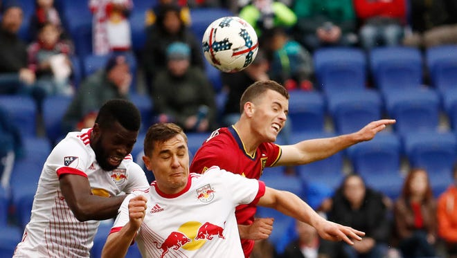 New York Red Bulls defender Kemar Lawrence, left, and teammate midfielder Aaron Long, center, go up for the ball against Real Salt Lake forward Brooks Lennon during the second half of an MLS soccer match, Saturday, March 25, 2017, in Harrison.