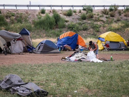 Residents of the tent city clean up trash left behind