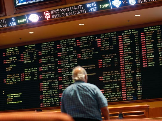 Betting odds are displayed on a board in the sports