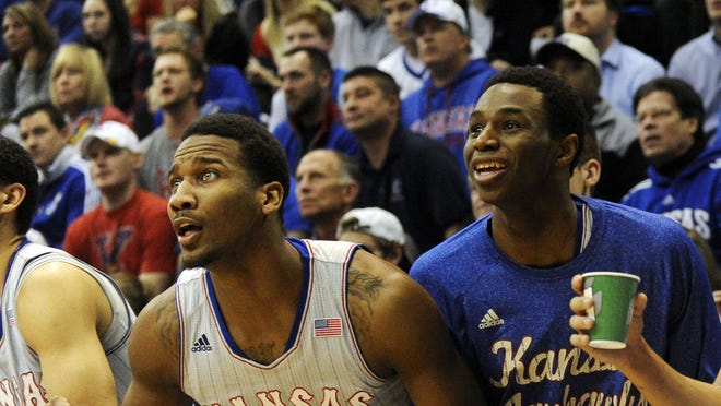 Kansas Jayhawks guard Wayne Selden, Jr. (left),  guard Andrew Wiggins (center) and Kansas Jayhawks guard Niko Roberts (right) celebrate a backed against the Texas Tech Red Raiders in the second half at Allen Fieldhouse. Kansas won the game 82-57.
