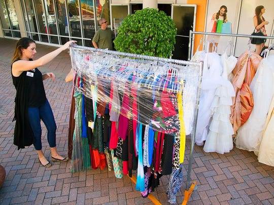 Allyson Ross, of PACE Center for Girls, Lee, prepares dresses for PACE's annual Love That Dress! fundraiser at the Embassy Suites Fort Myers-Estero in August 2016.