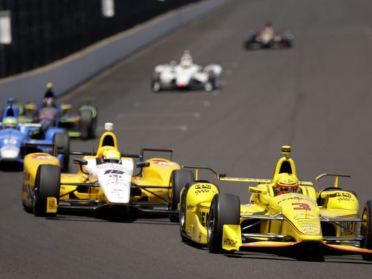 IndyCar driver Helio Castroneves leads a group of cars