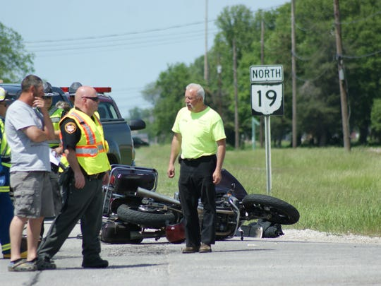 Authorities investigate the scene after a motorcycle crashed into a car Monday afternoon at Ohio 19 and County Road 73.