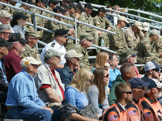 Spectators and shooters competing in rifle and pistol competitions watch the first shot ceremony held at Camp Perry.