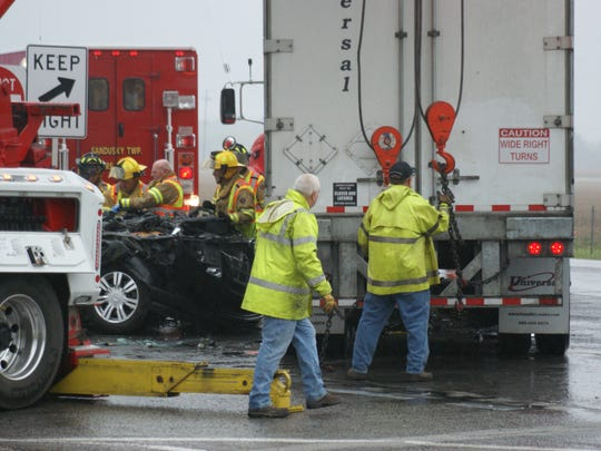 Emergency crews works to remove a trapped SUV from beneath a trailer when the two crashed Wednesday around 7:10 a.m. The driver of the Cadillac was pronounced dead at the scene.