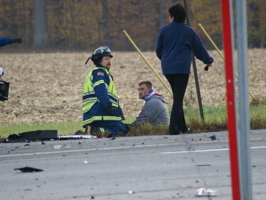 Jose Gonzales is evaluated by Sandusky County EMS after the fiery crash on U.S. 20 Thursday morning. He was later taken by EMS to Firelands Regional Medical Center in Sandusky, where he was treated for a broken shoulder blade.