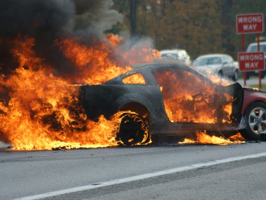 A Ford Mustang is engulfed in flames after two-vehicle