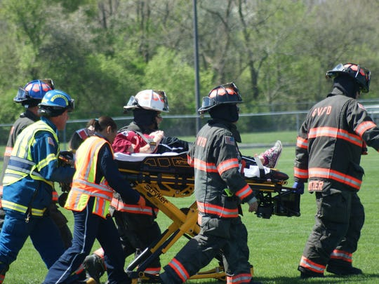 Anna Stout, a student at Gibsonburg High School, is carted off by rescue personnel to a Life Flight helicopter for treatment of injuries during a mock crash scenario at Gibsonburg High School Tuesday.
