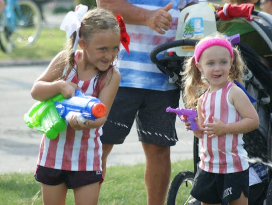 Keira, left, and Karson McNerney, right, play with water guns during the Squirt Gun Run in Port Clinton.