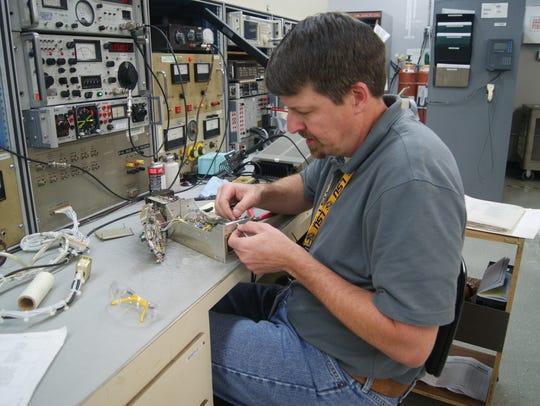An avionics repair technician works on a test bench