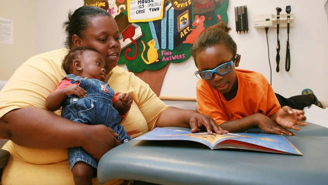 Vyanka Pruitt, of Cincinnati, and her children, Carlos, left, and Devonte, are among the first enrolled in the Reach Out and Read/Imagination Library program.