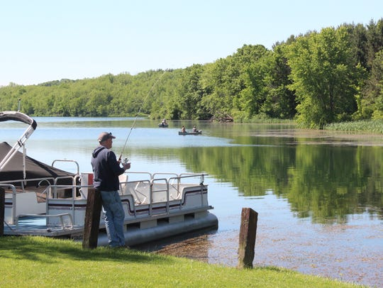 An angler fishes from shore of Blackhawk Lake near