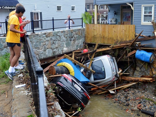 Residents gather by a bridge to look at cars left crumpled in one of the tributaries of the Patapsco River that burst its banks as it channeled through historic Main Street in Ellicott City, Md., on May 28, 2018.