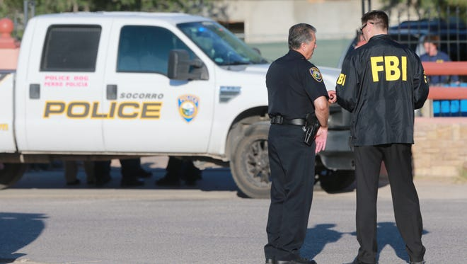 FBI agents talk with Socorro police officers during the execution of search warrants June 22, 2016.