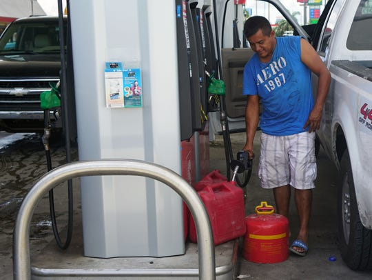 A man pumps gas into multiple containers at a gas station