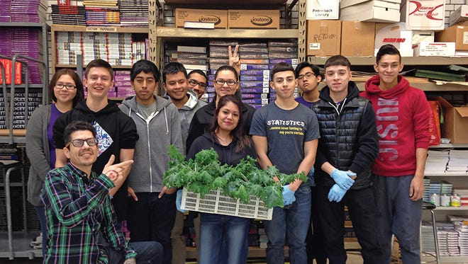 Students at Schurz High School in Chicago show off some greens grown in the school's Food Science Lab.