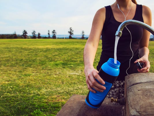 Female runner fills up water bottle outdoors