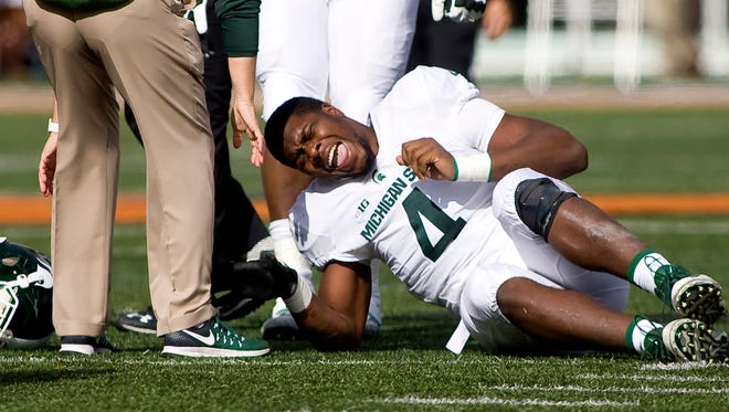 Michigan State Spartans defensive lineman Malik McDowell injures his ankle during the third quarter against the Illinois Fighting Illini at Memorial Stadium.