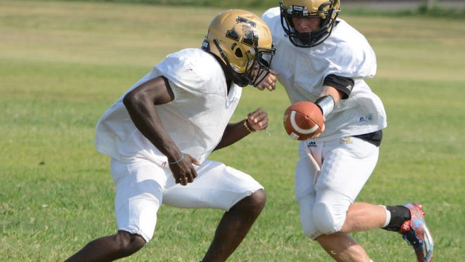 Abilene High quarterback Andrew Ezzell hands off to running back Niyungeko Moise during practice Tuesday at the Eagles' on-campus practice field.