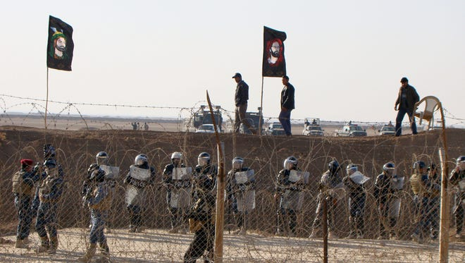 In this photo provided by the People's Mujahedeen Organization of Iran, Iraqi police stand guard in 2011 outside the opposition group's camp northeast of Baghdad.