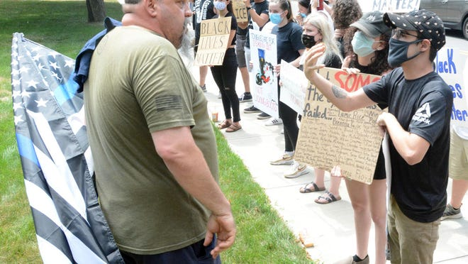 Josh Potter of Plainfield, right, and a supporter of the Back the Blue rally, left, who asked not to be identified, argue their opinions Saturday during a Back the Blue rally in support of police at Davis Park in Danielson. See videos and more photos at NorwichBulletin.com