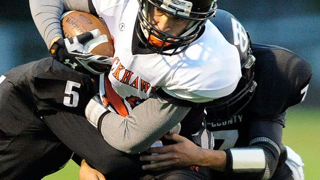 Port Edward's Ethan Saylor, center, runs for yardage, while being grabbed by Tri-County's Luke Marinack, left, and Brock Akkerman, right, during first-half action Friday Sept. 12, 2014 in Plainfield.